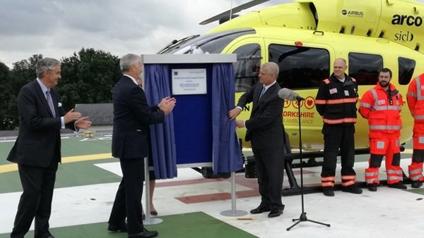 HRH the Duke of York unveils a plaque on the new helipad at Northern General Hospital, with a helicopter in the background